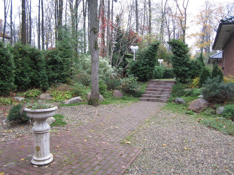 средний участок садовая ваза гравийная дорожка тротуарная плитка осень лестница липы лесной участок арка из туи валуны нагорье орех серый