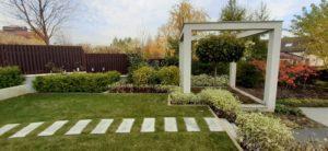 средний участок современный сад дорожка из слэбов гранитных плит светильники садовые живая изгородь из дерен пестролистный газон маф из бетона клен глобозум осень подпорная стенка из бетона пестово