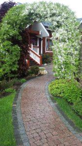 средний участок весна дорожка из гранитной брусчатки арка из яблони декоративной глаголево